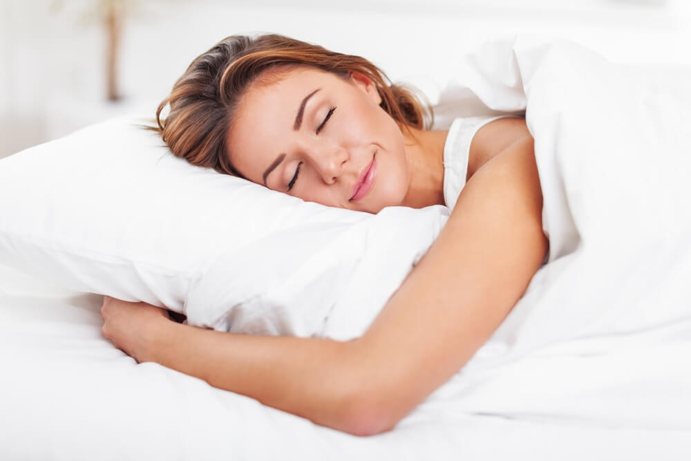 Young woman sleeping soundly on white sheets