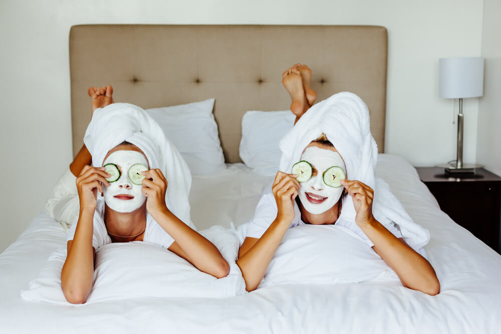 Friends enjoying home facial on bed