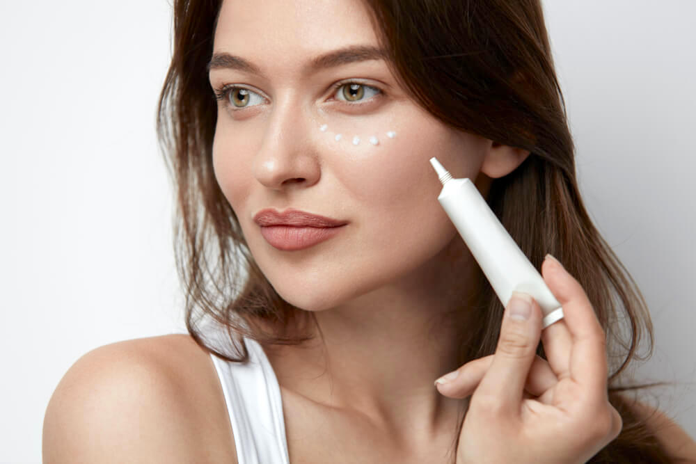 Young woman applying eye cream with an applicator